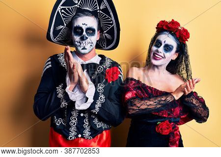 Young couple wearing mexican day of the dead costume over yellow clapping and applauding happy and joyful, smiling proud hands together
