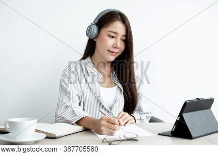 Female Asian College Student Wearing Headphones Enjoys Online Tutoring, Watching Videos And Taking N