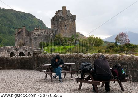 Eilean Donan, Scotland, August 09 2012: Tourist People Sitting Outside The Famous Eilean Donan Castl
