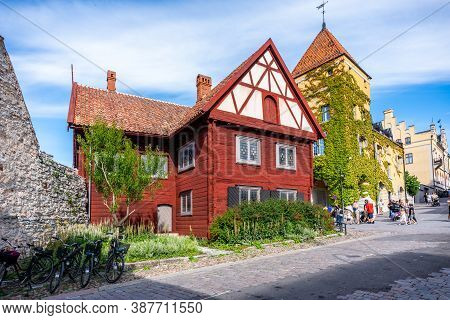 Visby, Sweden - July 27, 2020: Summer City View Of An Old Red Wooden Gothic Alp Building In The Hist