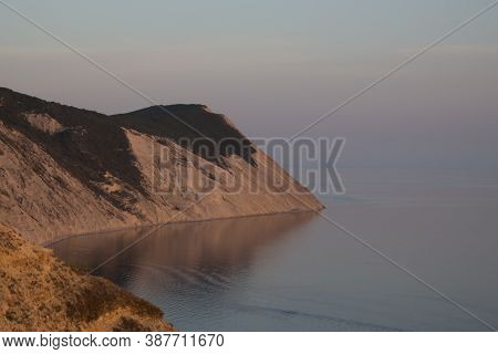 A Bay With A Beautiful Sheer Cliff At Sunset With Blue Sea Water. Rocks By The Ocean, Rocky Ledge, C