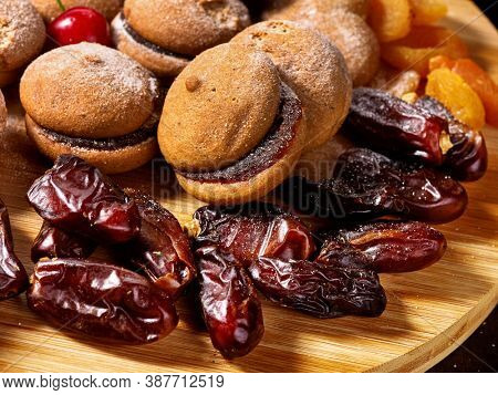 Oatmeal cookies and sand chocolate cake with cherry berry and dried fruits dates, apricots on cutting board on wooden table in rustic style.