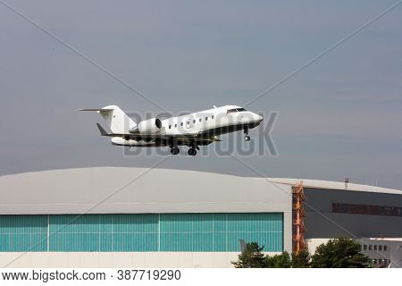 Corporate Business Jet Taking Off On The Background Of A Hangar