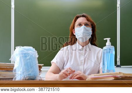 The School Doctor Sits In The Classroom And Distributes Medical Masks. School Nurse Handles Hands Wi