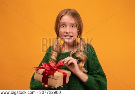 Image Of Charming Blonde Girl 12-14 Years Old In Warm Green Sweater Holding Present Box With Red Bow