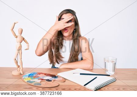 Beautiful young caucasian woman artist painter sitting on desk peeking in shock covering face and eyes with hand, looking through fingers afraid