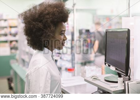 Black Female Pharmacist At Pharmacy. Close Up Side View Of Pretty Woman Pharmacist Working With Comp
