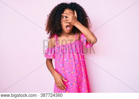 African american child with curly hair wearing casual dress peeking in shock covering face and eyes with hand, looking through fingers with embarrassed expression.