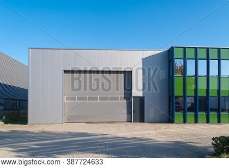 Modern Industrial Unit With Roller Doors Against A Blue Backgrouind