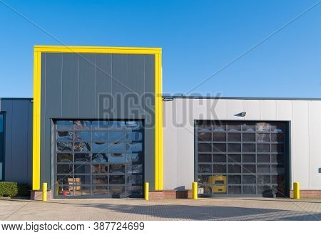Modern Industrial Unit With Roller Doors And Yellow Border