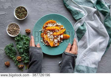 Tasty Pumpkin Salad With Feta,  Top View. Female Hands Hold A Plate With A Dish.