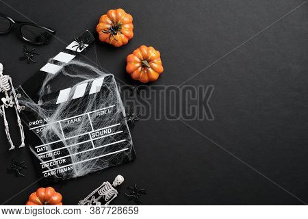 Movie Clapperboard And Halloween Decoration On Black Table. Horror Movie Night, Halloween Party Invi