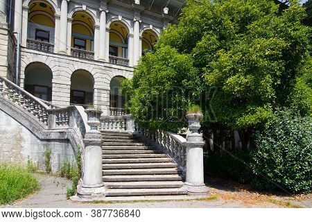 Old Building With A Stone Staircase In The Park. Ancient Staircase With Stone Balusters On A Backgro