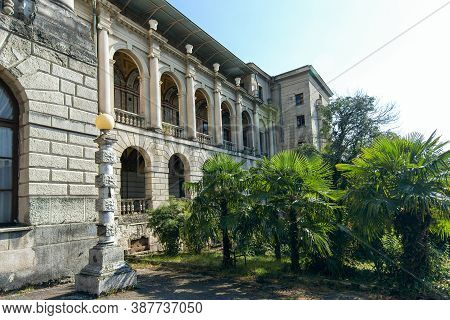 Old Grey Stone Building With Columns And Balconies And Balusters In A Park With Tropical Plants. Fro