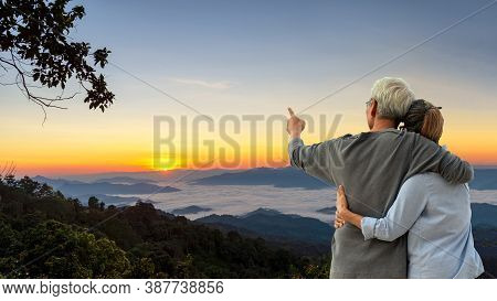 Asian Lifestyle Senior Couple Hug And Pointing The Mountain Field During Mist Sunrise Nature.  Old P