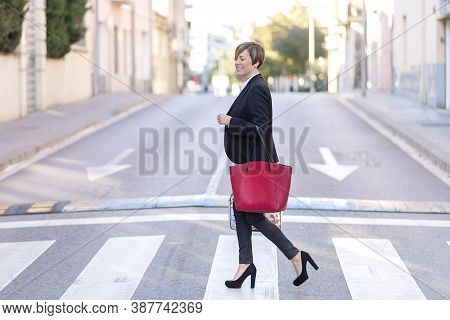 Businesswoman Walking On Crossroad Holding Red Bag