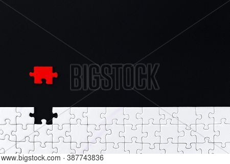 White Puzzles Are Stacked On Bottom Of Black Background. One Red Piece Located Separately On Distanc