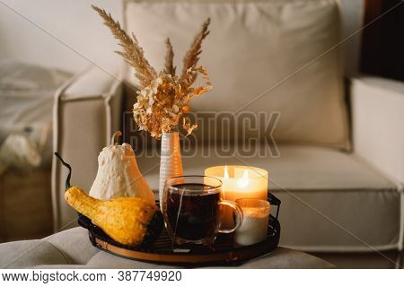 Still Life Details In Home Interior Of Living Room. Pumpkin And Cup Of Tea With Candles On A Serving