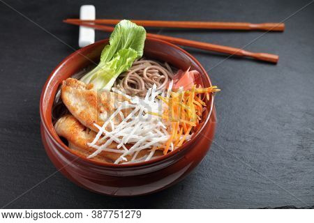 Portion of Soba noodle soup with slices of fried chicken, daikon radish, carrot, marinated ginger, and leafs of bok choy