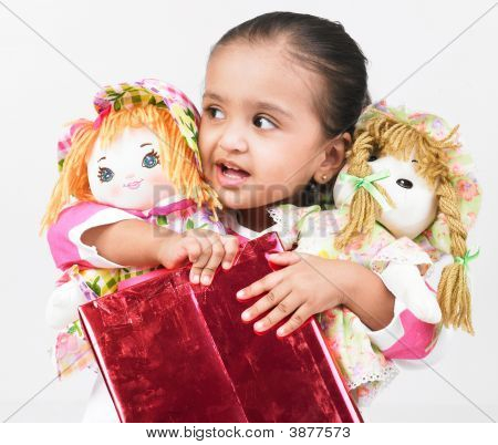 Asian Girl Holding Two Dolls And A Gift Box