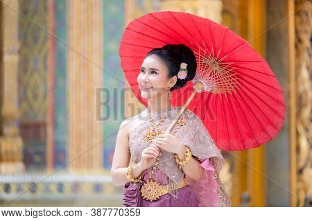 A Beautiful, Graceful Thai Woman In Thai Dress Adorned With Valuable Jewelry Holding Red Umbrella