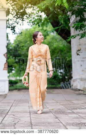 Elegant Thai Woman In Thai Dress Adorned With Precious Jewelry Walks Holding Flower Garlands In Thai