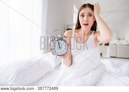 This Is Noon Omg. Photo Of Shocked Displeased Lady Sit Bed Sheets Hold Metal Alarm Clock Morning Mis