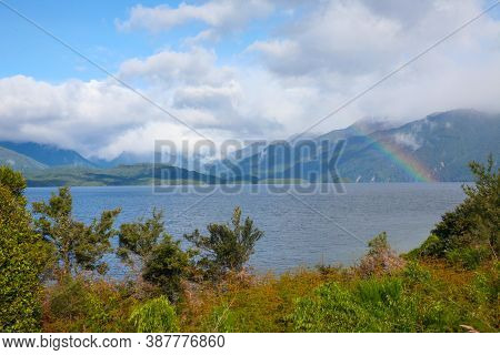 Wanaka Lakefront With Rainbow And Mountains, Central Otago, New Zealand