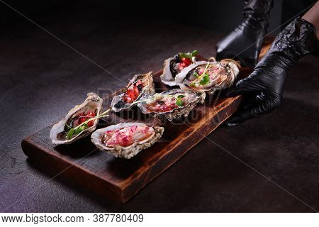 Two Types Of Oysters With Savory Sauces On A Wooden Board. Stylish Serving Dishes. Oyster Season. Un
