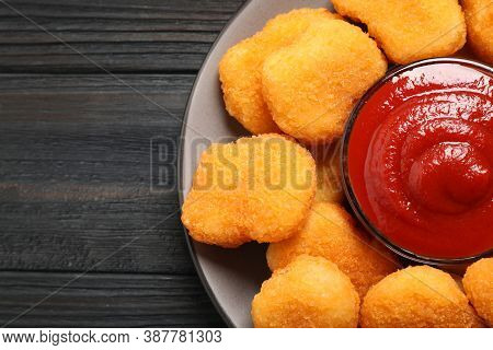 Tasty Fried Chicken Nuggets With Tomato Sauce On Black Wooden Table, Top View