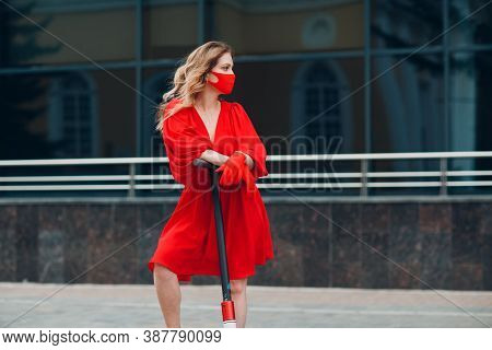 Young Woman With Electric Scooter In Red Dress And Gloves With Medical Face Mask At The City