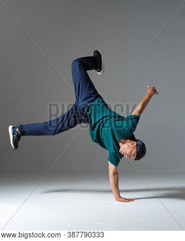 Cool Guy Breakdancer Dance On The Floor Isolated On Gray Background. Breakdance Lessons