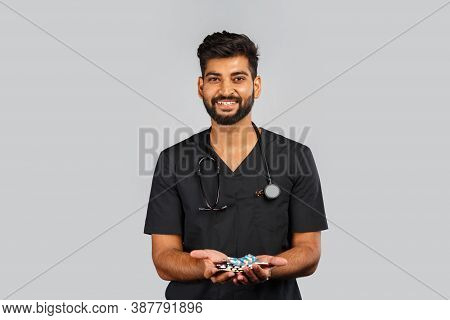 Cute Indian Doctor Or Surgeon In Black Uniform With Stethoscope And Pills On Gray Background