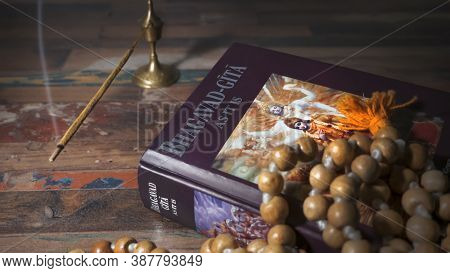 Bhagavad Gita And Rosary Lying On A Wooden Table And Incense Is Being Smoked.