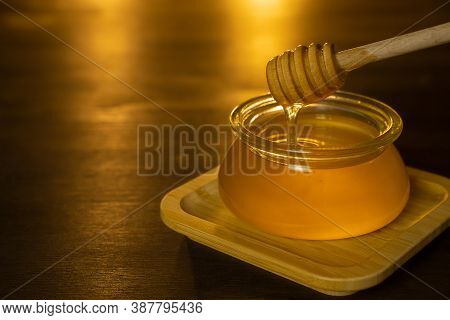 Honey Drips From A Honey Stick Into A Glass Pot. Thick Honey Dipped In A Wooden Honey Spoon, Close-u