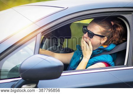 A Woman Drives A Car, A Woman In A Traffic Jam In Sunglasses, Yawns Covering Her Mouth. Fall Asleep