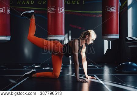 Blond Concentrated Woman Warming Up Doing Leg Stretch In Dark And Shiny Gym With Shadows And Punchin