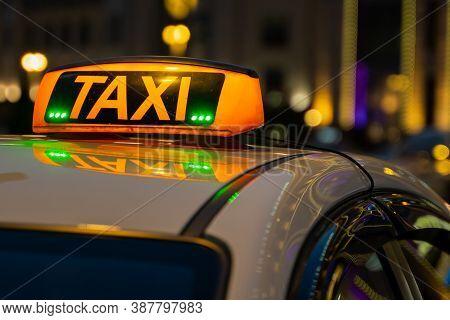 Illuminated Orange Taxi Sign On A White Car. Luminous Scoreboard.