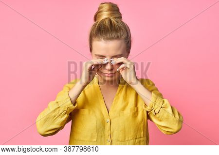 Young Woman In A Yellow T-shirt On A Pink Background Scratches Her Eyes.