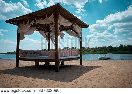 Weekend On Vacation On A Sandy Beach. Gazebo With Curtains On The River. Yacht Is Moored To Berth An