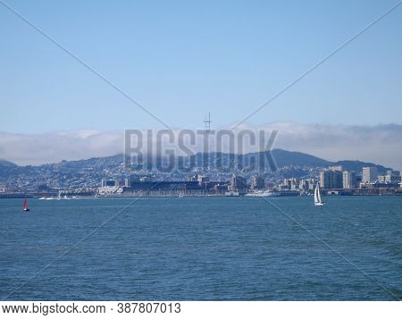 Sail Boats In Water Of San Francisco Bay With Cityscape In The Distance.