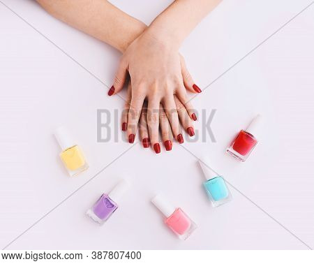 Nail Polish. Art Manicure. Multi-colored Nail Polish Bottles Around Female Hands With Stylish Red Na