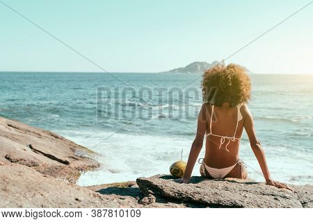 View From Behind Of A Young African-american Female With Curly Hair, In A Swimsuit Sitting On A Rock