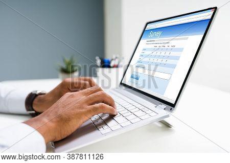 Man Filling Online Survey Form On Laptop Computer
