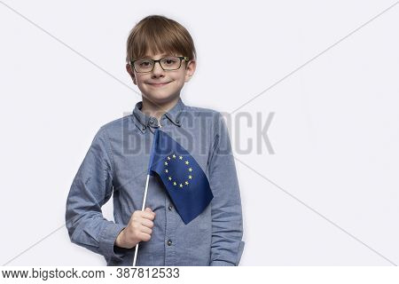 Serious Teen Boy Holding European Union Flag Isolated On White Background. Student With A Flag Of Eu