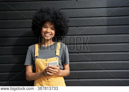 Happy African American Young Hipster Lady With Afro Hair Standing On Black Background Holding Smart