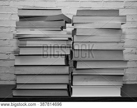 Black And White Image Of Some Books Stacked On A Shelf, Light Brick Background