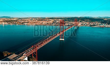 Aerial View Or Drone Photo Of The 25 De April Bridge. Red Bridge Is Connecting Lisbon And Almada, Po