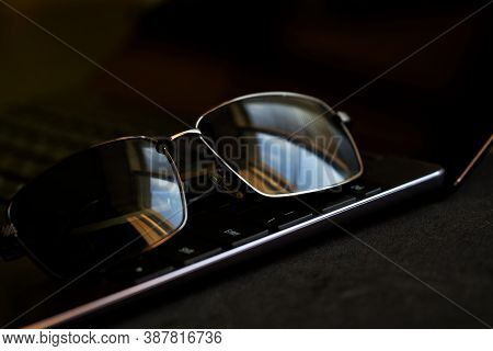 Black Sunglasses Lie On The Keyboard Of A Thin Laptop. The Problem Of Hacking, Espionage And The Dar