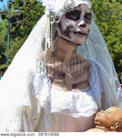 Cuenca, Ecuador - May 18, 2019: Unidentified Dreadful Zombie Woman Dressed As Bride Holds A Dead Bab